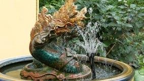 Τρεις-διευθυνμένος πράσινος δράκος ως παραδοσιακό βουδιστικό σύμβολο Άγαλμα και μια πηγή του δράκου στον κήπο της Ταϊλάνδης φιλμ μικρού μήκους