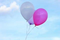 Τρεις επιπλέοντα μπαλόνια στο μπλε ουρανό ροζ μπαλονιών πορφυρό μπαλόνι Ιώδες μπαλόνι λευκό μπαλονιών Στοκ Φωτογραφία