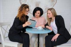 Τρεις επιχειρησιακές γυναίκες διοργανώνουν μια συνεδρίαση Στοκ Εικόνες