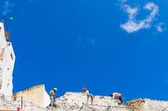 Τρεις εργάτες οικοδομών εργάζονται σε ένα παλαιό κτήριο με το μπλε ουρανό Στοκ εικόνες με δικαίωμα ελεύθερης χρήσης