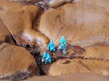 Τρεις εργαζόμενοι σκάβουν στο κέικ σοκολάτας Στοκ εικόνα με δικαίωμα ελεύθερης χρήσης