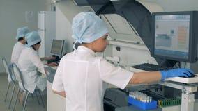 Τρεις εργαστηριακοί εργαζόμενοι σε ένα σύγχρονο εργαστήριο απόθεμα βίντεο
