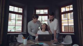 Τρεις ευτυχείς άνθρωποι που κοιτάζουν στην οθόνη και το χαμόγελο PC απόθεμα βίντεο