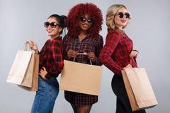 Τρεις ευτυχείς γυναίκες στα γυαλιά ηλίου Αμερικανικές, ασιατικές και καυκάσιες φυλές Afro Αγορές με απομονωμένος στο γκρίζο υπόβα στοκ φωτογραφία