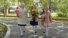 Τρεις ευτυχείς μαθήτριες με τις ανθοδέσμες λουλουδιών που πηγαίνουν πίσω στο σχολείο απόθεμα βίντεο