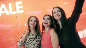 Τρεις ευτυχείς νέες γυναίκες που παίρνουν τις φωτογραφίες στο εμπορικό κέντρο που στέκεται στο κόκκινο κλίμα φιλμ μικρού μήκους