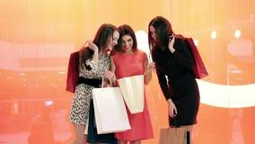 Τρεις ευτυχείς ψωνίζοντας γυναίκες που στέκονται στο κόκκινο κλίμα και που συζητούν τις αγορές τους φιλμ μικρού μήκους