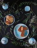 Τρεις εύγευστες βάφλες, μπισκότα μελοψωμάτων είναι τα μπλε πιάτα με τα χορτάρια και λουλούδια σε μια μαύρη φωτογραφία τροφίμων κι στοκ εικόνες