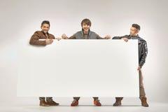 Τρεις εύθυμοι τύποι που κρατούν τον πίνακα Στοκ εικόνα με δικαίωμα ελεύθερης χρήσης