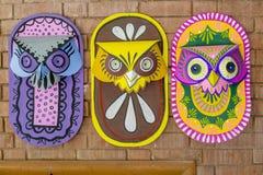 Τρεις ζωηρόχρωμες μάσκες κουκουβαγιών που κρεμούν στον τοίχο ιδρυμάτων τέχνης Στοκ φωτογραφίες με δικαίωμα ελεύθερης χρήσης