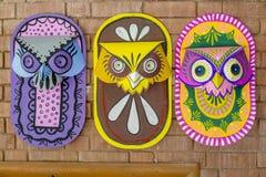 Τρεις ζωηρόχρωμες μάσκες κουκουβαγιών που κρεμούν στον τοίχο ιδρυμάτων τέχνης Στοκ φωτογραφία με δικαίωμα ελεύθερης χρήσης