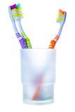 Τρεις ζωηρόχρωμες οδοντόβουρτσες στο γυαλί, δύο ενάντια σε ένα Στοκ Εικόνες
