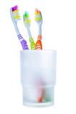 Τρεις ζωηρόχρωμες οδοντόβουρτσες στο γυαλί Στοκ Εικόνες