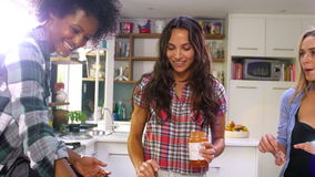 Τρεις θηλυκοί φίλοι που κατασκευάζουν την πίτσα στην κουζίνα από κοινού απόθεμα βίντεο