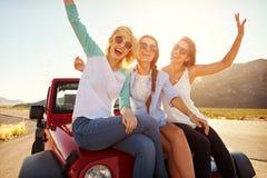 Τρεις θηλυκοί φίλοι στο οδικό ταξίδι κάθονται στην κουκούλα αυτοκινήτων στοκ εικόνες