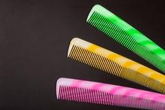 Τρεις διαφορετικές χρωματισμένες βούρτσες γηα τα μαλλιά σε ένα σκοτεινό υπόβαθρο Στοκ φωτογραφίες με δικαίωμα ελεύθερης χρήσης