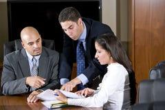 Τρεις ισπανικοί εργαζόμενοι γραφείων που αναθεωρούν την έκθεση στοκ εικόνα