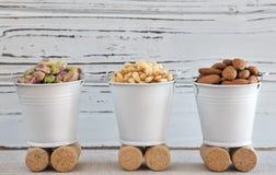 Τρεις κάδοι των καρυδιών στο ξύλινο υπόβαθρο Στοκ εικόνα με δικαίωμα ελεύθερης χρήσης