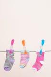 Τρεις κάλτσες μωρών που κρεμιούνται για να ξεράνουν Στοκ Εικόνες