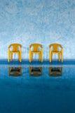 Τρεις κίτρινες καρέκλες στην πισίνα Στοκ Εικόνες