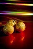 Τρεις κίτρινες σφαίρες Χριστουγέννων στο κόκκινο υπόβαθρο στοκ εικόνες