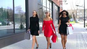 Τρεις καλές νέες γυναίκες που περπατούν κάτω από την οδό και που απολαμβάνουν την ημέρα αγορών τους Νέες γυναίκες στα όμορφα φορέ απόθεμα βίντεο