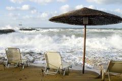 Τρεις καρέκλες και ένας θόλος ήλιων σε μια θυελλώδη παραλία στοκ φωτογραφία με δικαίωμα ελεύθερης χρήσης