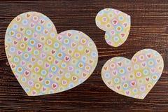 Τρεις καρδιές εγγράφου στο ξύλινο υπόβαθρο Στοκ Εικόνες