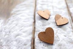 Τρεις καρδιές με τις επιγραφές της αγάπης στο υπόβαθρο των πινάκων δεν είναι το υπόβαθρο του χιονιού, ημέρα βαλεντίνων ` s Στοκ φωτογραφία με δικαίωμα ελεύθερης χρήσης