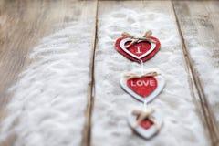 Τρεις καρδιές με τις επιγραφές της αγάπης στο υπόβαθρο των πινάκων δεν είναι το υπόβαθρο του χιονιού, ημέρα βαλεντίνων ` s Στοκ φωτογραφίες με δικαίωμα ελεύθερης χρήσης