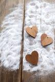 Τρεις καρδιές με τις επιγραφές της αγάπης στο υπόβαθρο των πινάκων δεν είναι το υπόβαθρο του χιονιού, ημέρα βαλεντίνων ` s Στοκ Φωτογραφία