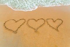 Τρεις καρδιές που επισύρονται την προσοχή στην αμμώδη παραλία με την προσέγγιση κυμάτων Στοκ φωτογραφία με δικαίωμα ελεύθερης χρήσης