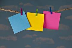 Τρεις κενές ζωηρόχρωμες σημειώσεις που ψαλιδίζονται στη σκοινί για άπλωμα σπάγγου με τα clothespins μπροστά από τον όμορφο μπλε ου στοκ φωτογραφίες