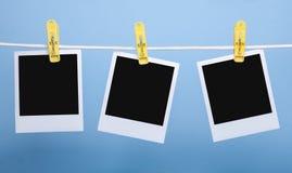 Τρεις κενές κάρτες φωτογραφιών που απομονώνονται στο μπλε υπόβαθρο στοκ φωτογραφία