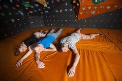 Τρεις κουρασμένοι ορειβάτες στο χαλί κοντά στον τοίχο βράχου στο εσωτερικό Στοκ εικόνα με δικαίωμα ελεύθερης χρήσης