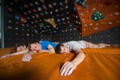 Τρεις κουρασμένοι ορειβάτες στο χαλί κοντά στον τοίχο βράχου στο εσωτερικό Στοκ Φωτογραφίες