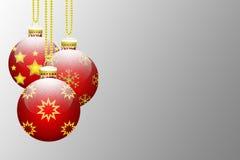 Τρεις κόκκινες κρεμώντας σφαίρες χριστουγεννιάτικων δέντρων που καλύπτονται με το χιόνι ελεύθερη απεικόνιση δικαιώματος