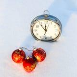 Τρεις κόκκινες σφαίρες Χριστουγέννων και wath σε ένα χιόνι Στοκ Εικόνες
