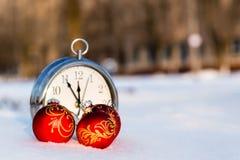 Τρεις κόκκινες σφαίρες Χριστουγέννων και wath σε ένα χιόνι Στοκ Φωτογραφίες