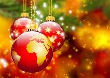 Τρεις κόκκινες σφαίρες Χριστουγέννων που κρεμούν μπροστά από το αφηρημένο δέντρο του FIR Στοκ εικόνες με δικαίωμα ελεύθερης χρήσης