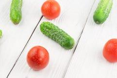 Τρεις κόκκινες ώριμες ντομάτες και πολλά φρέσκα πράσινα αγγούρια που διασκορπίζονται στο ξύλινο υπόβαθρο στοκ φωτογραφία
