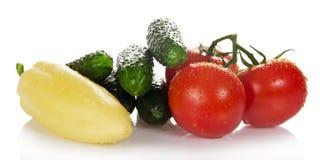 Τρεις κόκκινοι ντομάτες και σωρός των αγγουριών Στοκ εικόνα με δικαίωμα ελεύθερης χρήσης