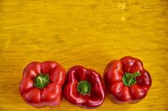 Τρεις κόκκινος στενός επάνω πιπεριών κουδουνιών στο ξύλινο κίτρινο υπόβαθρο με το διάστημα αντιγράφων Τα πιπέρια κουδουνιών στην  Στοκ Φωτογραφίες