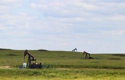 Τρεις λειτουργώντας γρύλοι αντλιών στα φρεάτια πετρελαίου ή αερίου έξω σε έναν πράσινο τομέα στοκ φωτογραφία με δικαίωμα ελεύθερης χρήσης