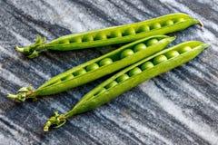 Τρεις λοβοί των πράσινων μπιζελιών που βρίσκονται σε ένα πιάτο γρανίτη Στοκ Φωτογραφίες