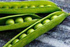 Τρεις λοβοί των πράσινων μπιζελιών που βρίσκονται σε ένα πιάτο γρανίτη Στοκ φωτογραφίες με δικαίωμα ελεύθερης χρήσης