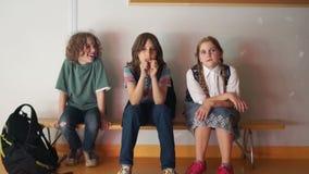 Τρεις μαθητές κάθονται σε έναν πάγκο στο σχολικό διάδρομο, περιμένοντας την έναρξη των κατηγοριών o απόθεμα βίντεο