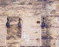 Τρεις μαύροι λαμπτήρες στον αρχαίο τοίχο πετρών στοκ εικόνες