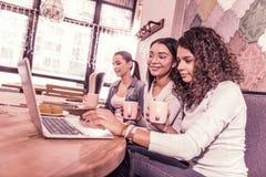Τρεις μεταπτυχιακοί σπουδαστές που εργάζονται στο πρόγραμμά τους συνανμένος στο αρτοποιείο στοκ εικόνες
