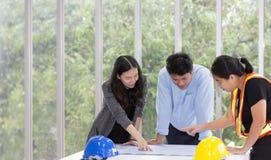 Τρεις μηχανικοί που απασχολούνται στην αίθουσα συνεδριάσεων στο γραφείο Εργαζόμενος τρία στοκ φωτογραφίες